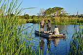 iSimangaliso Wetlands Park. Visitors crossing a river with a local raffia boat. Santa Lucia. Kwazulu Natal. South Africa.