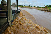 4x4 crossing the Mara river during the rainy season, Masai Mara national park, Kenya.