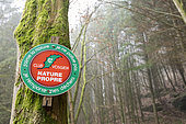 Sign of the Vosges club on a tree, sensitizing hikers to keep the forest clean, winter, Moselle, France