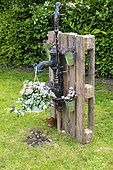 Garden decoration composed of a pump fixed on a recovery pallet, spring, Pas de Calais, France