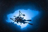 Inside the reef. Underwater photographer in an underwater cave, Misool, Raja Ampat, Indonesia