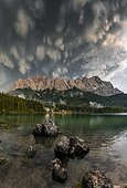 Rocks on the shore, Eibsee lake in front of Zugspitze massif with Zugspitze, sunset, dramatic Mammaten clouds, Wetterstein range, near Grainau, Upper Bavaria, Bavaria