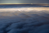 Sea of night clouds, lit by Aix les Bains and Chambéry. Stratus on the Savoyard valleys, during a marked temperature inversion. Shooting from Mont Revard. Savoy, France