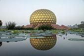 """Le Matrimandir et son jardin. Auroville, """"la ville de l'Aurore"""", cité expérimentale, idéale, universelle, est née d'un rêve de Mirra Alfassa, nommée """"La Mère"""", et de Sri Aurobindo. Elle a été inaugurée en 1968, accueille des gens du monde entier, partageant la volonté de réaliser l'unité humaine. Le Matrimandir, cette gigantesque boule dorée est un lieu de méditation pour une nouvelle conscience, et rayonne depuis le centre de la ville. Ici, une salutation du matin devant la sphère."""