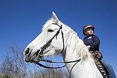 Léa, 8, rides her mare called Brume along the canals, Saintes-maries-de-la-mer, Camargue, France