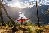 Woman with a sun hat sitting in an orange hammock, panoramic view of mountains with lake, Plansee, Tyrol, Austria, Europe