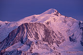 Mont-Blanc and Goûter huts lit by the Alpenglow, Haute-Savoie, France. Shot from Sallanches, in February 2020. The alpenglow is an optical phenomenon that appears after sunset. The rays of the sun are reflected by the cloud layer and give a red or pink tint to the Alpine massifs.