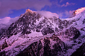 Aiguille du Midi lit by the Alpenglow. Shooting from Les Houches, in February 2020. Haute-Savoie, France. The alpenglow is an optical phenomenon that appears after sunset. The rays of the sun are reflected by the cloud layer and give a red or pink tint to the Alpine massifs.