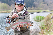 Fly fishing in a reservoir, Presentation of a rainbow trout (Oncorhynchus mykiss or Salmo gairdneri), Moselle, Lorraine, France