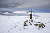 Aubrac plateau, granite cross and Lac des Moines frozen in ice, Aubrac regional natural park, Lozère, France