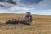 Farmer stubble ploughing his field, Escalles, Pas de Calais, France
