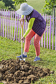 Woman digging up a patch of land before setting up a vegetable patch