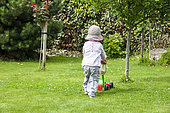 Girl playing with her lawnmower in a garden, summer, Pas-de-Calais, France
