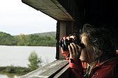 Girl observing birds through binoculars, Étang de la Véronne, Etangs du Malsaucy et de la Véronne trail, Sermamagny, Territoire de Belfort, France