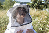Portrait of a 7 year old girl with a beekeeping suit, around Cluny, France