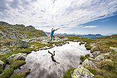 Hiker jumps, reflection in a small lake, Schladminger Höhenweg, Schladminger Tauern, Schladming, Styria, Austria, Europe