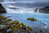 Long time exposure of a turquoise waterfall in volcanic landscape with dramatic clouds and green moss on rocks, Godafoss, Þingeyjarsveit, Norðurland eystra, Iceland
