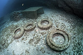 Photo denunciation, garbage in the sea, tire on submarine background. No matter the place if not the consequences.