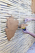 Application of a raw earth coating on a wall prepared with reeds, France