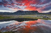 Mountain range reflected in the lake in evening mood with red clouds, Gällivare, Norrbottens län, Sweden, Europe
