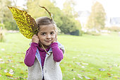 Girl making rabbit ears with dead leaves, autumn, Somme, France