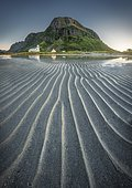 Gimsoy church reflected in the sea at low tide, in front sand beach with ribbed structure, behind mountain in evening sun, green vegetation on mountain slopes, Lofoten, Nordland, Norway, Europe