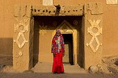 Young girl in traditional clothing in front of a mud house, Agadez, Niger, Africa
