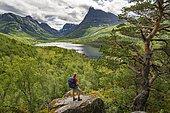 Hiker looking at high valley Innerdalen with lake Innerdalsvatna, mountains, right Innerdalstårnet, Trollheimen Mountain Area, Sunndal, Møre og Romsdal, Vestlandet, Norway, Europe