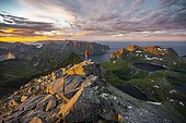 Hiker stands at the summit, sunset with dramatic clouds, view from the top of Hermannsdalstinden, fjords, lakes and mountains, Moskenesøya, Lofoten, Nordland, Norway, Europe
