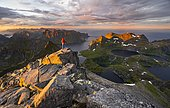 Hiker at the summit, evening mood, mountain landscape with Reinefjord and lake Krokvatnet, view from the summit of Hermannsdalstinden, Moskenesöy, Lofoten, Nordland, Norway, Europe