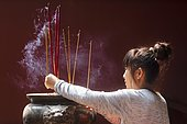 Young woman with burning incense sticks on Chinese New Year, temple complex Wat Phnom Daun Penh, Phnom Penh, Cambodia, Asia