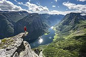 Hiker standing on rocky outcrop, view from the top of Breiskrednosi, mountains and fjord, Nærøyfjord, Aurland, Norway, Europe