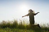 Girl running through a summer meadow in back light