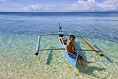 Young Filipino sits on small outrigger boat at Bounty Beach, Malapascua, Cebu, Philippines, Asia