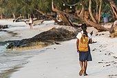 Local girls walking to school on idyllic sandy beach at Koh Tui Beach, Koh Touch village, Koh Rong island, Krong Preah Sihanouk, Sihanoukville, Cambodia, Asia