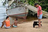 Jeune singe atèle ou singe araignée noir (Ateles paniscus) jouant avec des enfants sur une plage en Guyane Française