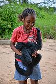 Jeune singe atèle ou singe araignée noir (Ateles paniscus) jouant et mordant une fillette sur une plage de Guyane Française
