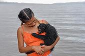 Jeune singe atèle ou singe araignée noir (Ateles paniscus) dans les bras d'une jeune femme sous la pluie en Guyane Française