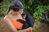 Jeune singe atèle ou singe araignée noir (Ateles paniscus) blotti dans les bras d'une jeune femme en Guyane Française