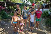 Groupe de personnes détenant un jeune singe atèle ou singe araignée noir (Ateles paniscus) en Guyane Française
