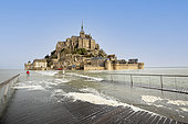 Baie du Mont-Saint-Michel, listed as World Heritage by UNESCO, the Mont surrounded by water from the footbridge during a high tide, tourists watch the show and wait for the drop in the tide to pass, Manche, France