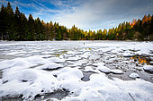 Snow-covered high altitude lake in the rising sun, Vosges, France.