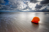 Buoy on the sand at low tide, pink granite coast, Brittany, France.