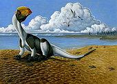 A Dilophosaurus dinosaur sitting in mud.