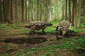 Two Hylaeosaurus drinking from a puddle in the forest, watching to avoid being surprised by a predator.