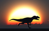 A silhouetted Allosaurus sprinting against a setting Sun at the end of another Jurassic day.