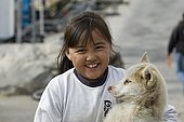 Young Inuk girl with a greenland dog puppy, Umanak, Greenland, North America