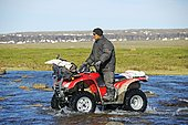 Man of the Inuit people riding a quad bike, ATV, through a river in the tundra on Victoria Island, formerly Holman Island, village of Ulukhaktok, Northwest Territories, Canada, North America