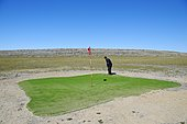 Man hitting a golf ball on the northernmost golf course in the world, Victoria Island, formerly Holman Island, village of Ulukhaktok, Northwest Territories, Canada, North America