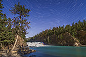 The stars of the northern sky circling in star trails over Bow Falls, on the Bow River in Banff, Alberta. A faint moonbow can be seen at right oer the falls.